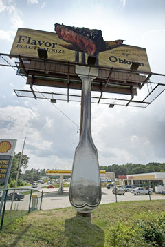 Sniffing for customers, N.C. 150 billboard wafts odor of grilling steak toward road.